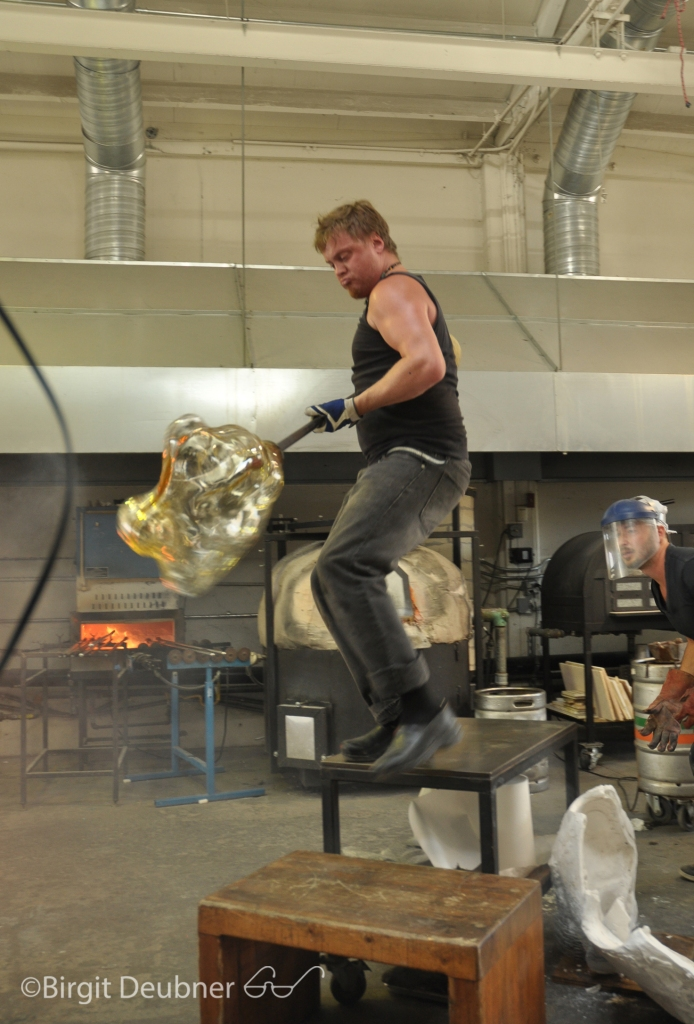 Alex Abajian holding the blowpipe with the large body cast glass (project for Ivan Mora)