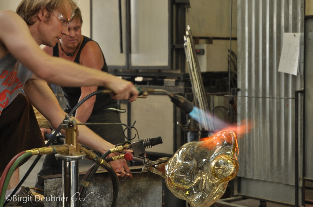 Jason torching the large glass body cast to keep it at even temperature to protect it from cracking before it can be placed into the annealer for a day long, controlled cooling process.. Project by Glass Artist: Ivan Mora