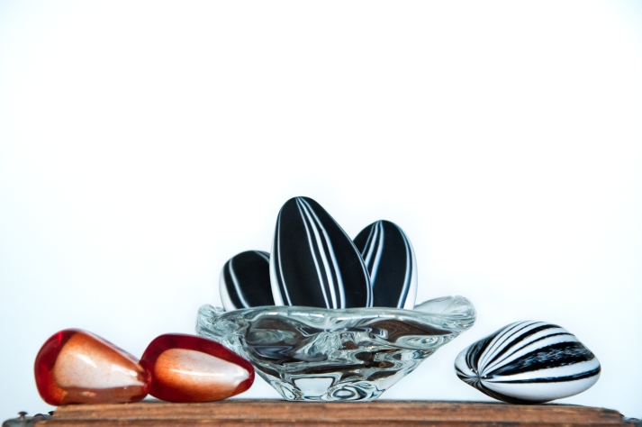 Jason Stropko Glass, arrangement of glass sunflower seeds, in clear glass bowl with red sculpted glass pomegranate seeds